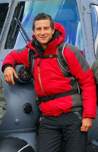 A photo of Bear Grylls standing in front of an Alaska Air National Guard helicopter.